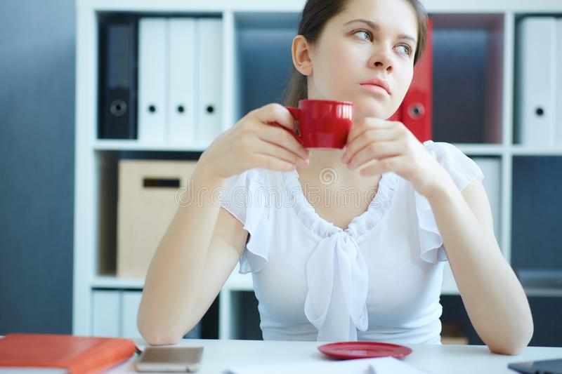 Beautiful young thoughtful business woman begins her morning with cup of coffee. stock photography