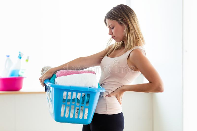 Beautiful young tired woman with back pain holding basket with clean clothes at home. Shot of beautiful young tired woman with back pain holding basket with royalty free stock photography