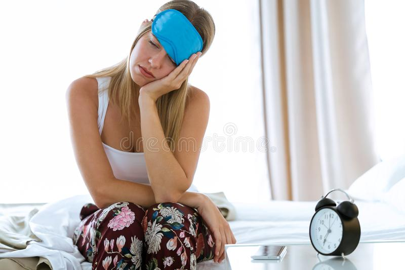 Beautiful young tired woman sitting on bed with sleep mask trying to wake up in bedroom at home. royalty free stock photos