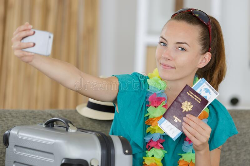 Beautiful young tourist girl taking funny selfie with passport royalty free stock photo