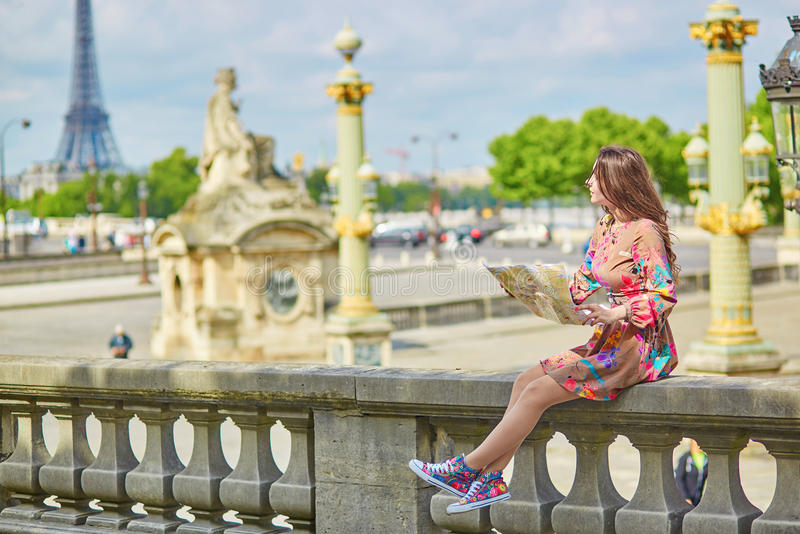 beautiful young tourist with map of paris in tuileries garden on a sunny summer day