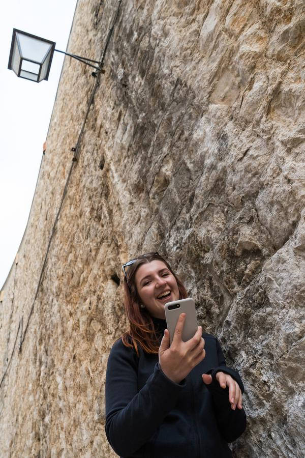 Beautiful young tourist woman visiting city sightseeing on stone wall, holding smartphone taking selfies photos, networking. Outdoors. Female using technology royalty free stock photography