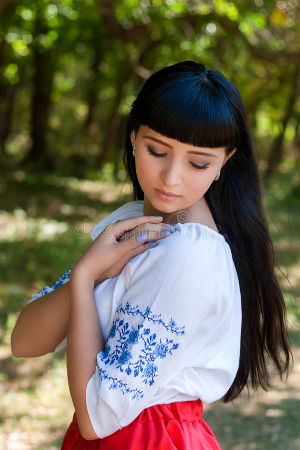 Beautiful young Ukrainian girl in national costume. Girl with beautiful appearance in the woods on the nature. Portrait royalty free stock photo