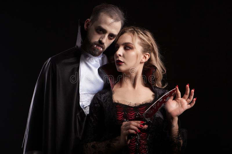 Beautiful young vampire woman with a blade covered in blood looking at her man dressed up like Dracula for halloween stock photography