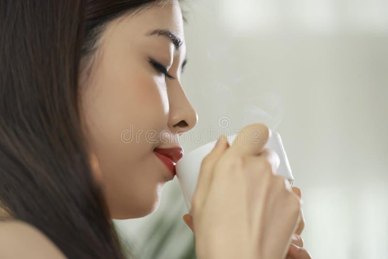 Woman drinking tasty coffee stock photo