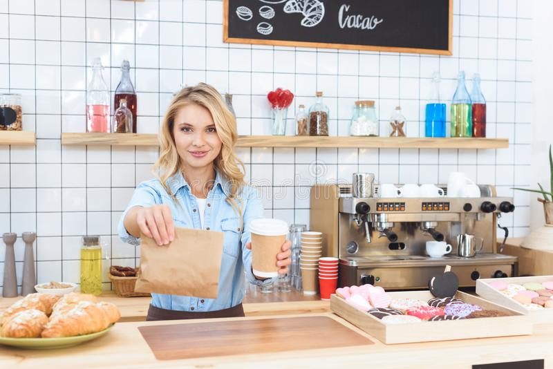 beautiful young waitress holding coffee to go and take away food stock image
