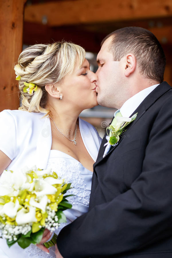 Beautiful young wedding couple outdoor. Bride with bouquet kissing her groom stock photo