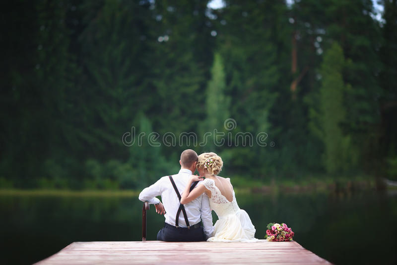 Beautiful young wedding couple sitting on the pier. royalty free stock photos