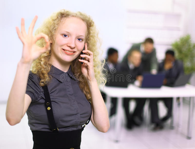 Beautiful young woman. Closeup of beautiful young woman speaking on cell phone with team in background royalty free stock image