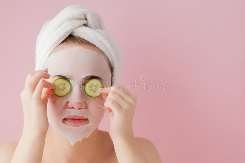 Beautiful young woman is applying a cosmetic tissue mask on a face with cucumber on a pink background. Beautiful young woman is appl cosmetic tissue mask on a stock photos