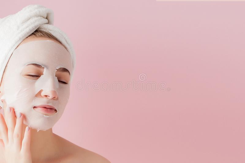 Beautiful young woman is applying a cosmetic tissue mask on a face on a pink background. Healthcare and beauty treatment and. Beautiful young woman is appl royalty free stock images