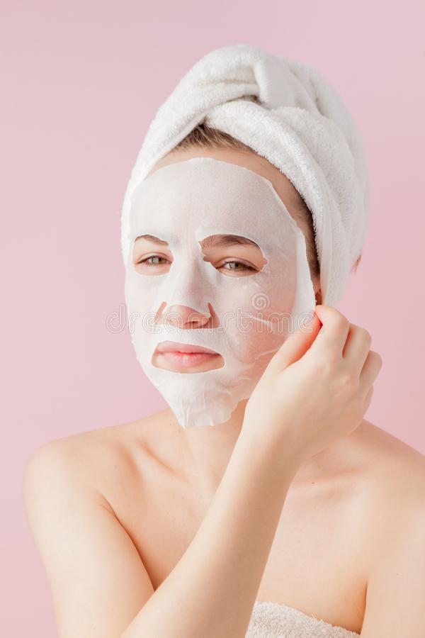 Beautiful young woman is applying a cosmetic tissue mask on a face on a pink background. Healthcare and beauty treatment and royalty free stock photography