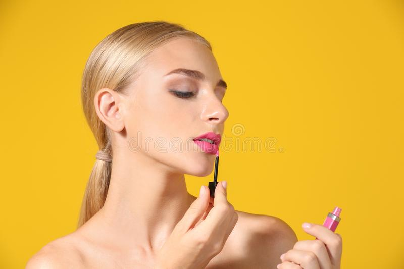Beautiful young woman applying bright pink lipstick on color background royalty free stock image