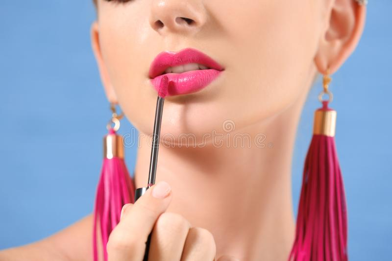 Beautiful young woman applying bright pink lipstick on color background, closeup royalty free stock images