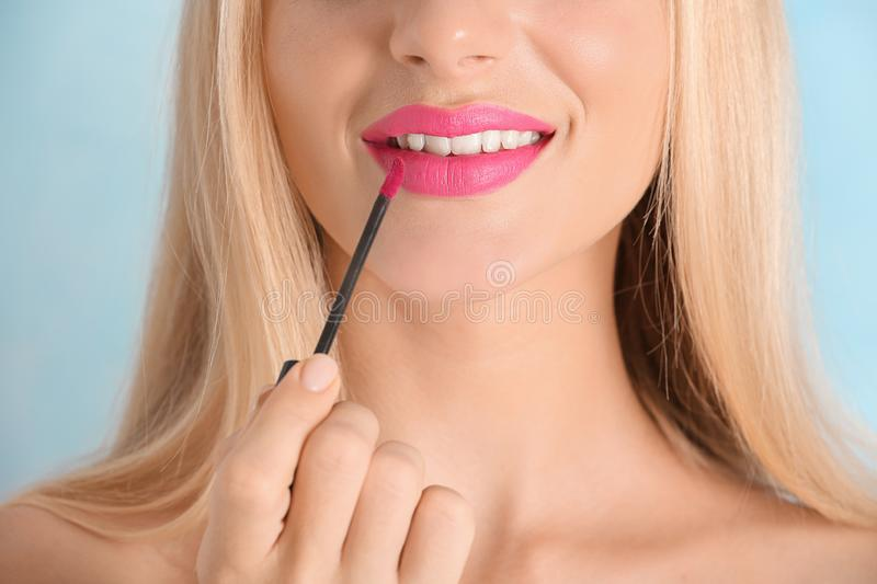 Beautiful young woman applying bright pink lipstick on color background, closeup royalty free stock image