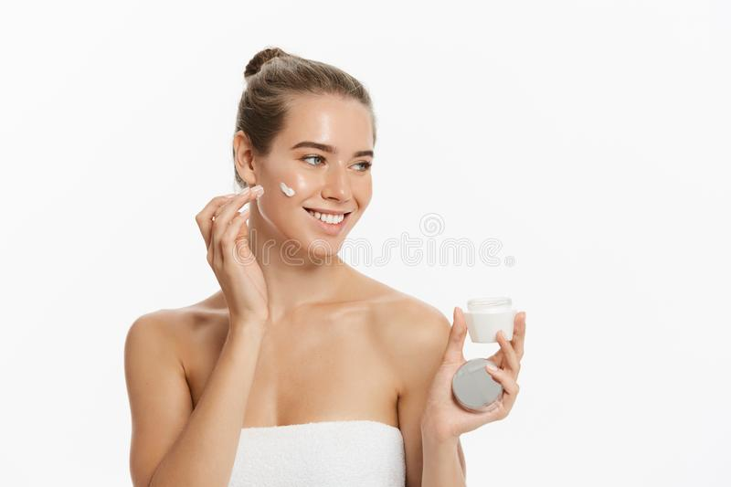 Beautiful young woman applying cosmetic cream treatment on her face isolated on white background royalty free stock photography