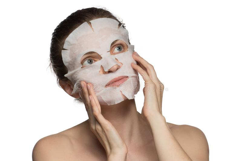 Beautiful young woman is applying a cosmetic mask on a face on a stock image