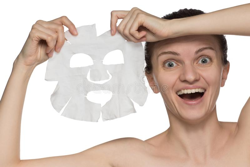 Beautiful young woman is applying a cosmetic mask and smiling on stock image