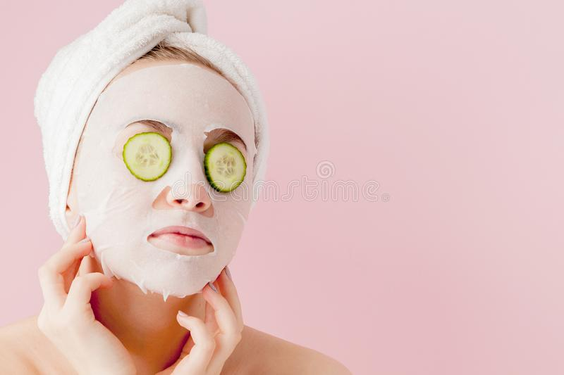 Beautiful young woman is applying a cosmetic tissue mask on a face with cucumber on a pink background.  stock images