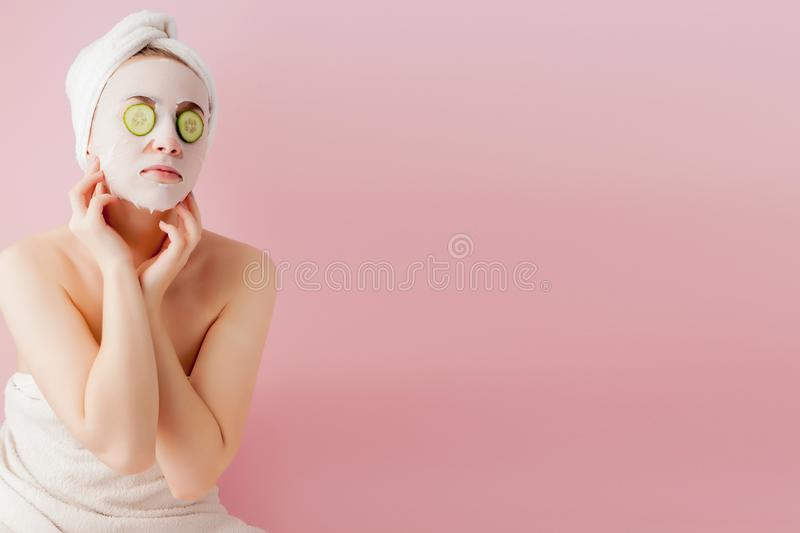 Beautiful young woman is applying a cosmetic tissue mask on a face with cucumber on a pink background.  royalty free stock photos