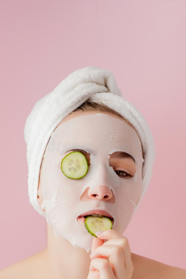 Beautiful young woman is applying a cosmetic tissue mask on a face with cucumber on a pink background stock images