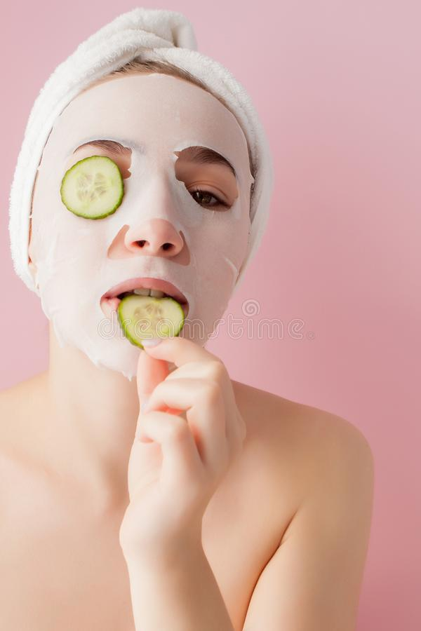 Beautiful young woman is applying a cosmetic tissue mask on a face with cucumber on a pink background.  stock photos