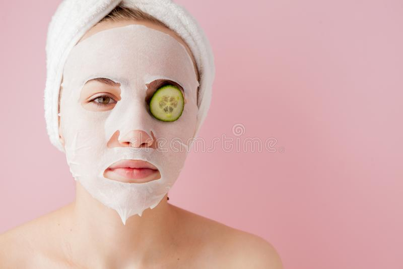 Beautiful young woman is applying a cosmetic tissue mask on a face with cucumber on a pink background. Healthcare and beauty. Treatment and technology concept stock photography