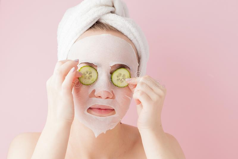 Beautiful young woman is applying a cosmetic tissue mask on a face with cucumber on a pink background. Healthcare and beauty. Treatment and technology concept stock photo