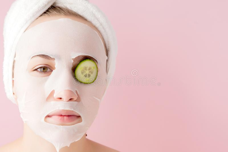 Beautiful young woman is applying a cosmetic tissue mask on a face with cucumber on a pink background. Healthcare and beauty. Treatment and technology concept royalty free stock images