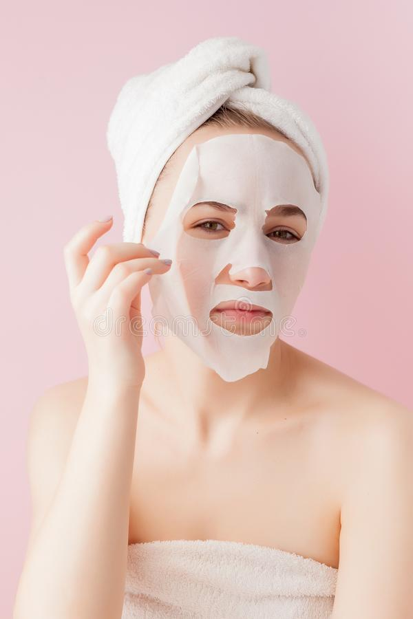 Beautiful young woman is applying a cosmetic tissue mask on a face on a pink background.  stock images