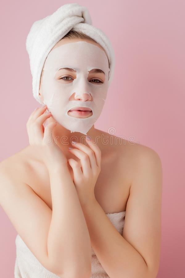 Beautiful young woman is applying a cosmetic tissue mask on a face on a pink background stock photo