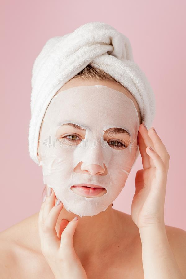 Beautiful young woman is applying a cosmetic tissue mask on a face on a pink background. Healthcare and beauty treatment and. Technology concept royalty free stock images