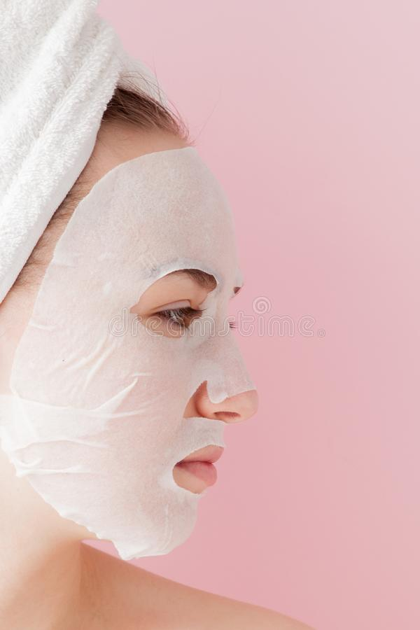 Beautiful young woman is applying a cosmetic tissue mask on a face on a pink background. Healthcare and beauty treatment and. Technology concept royalty free stock photo