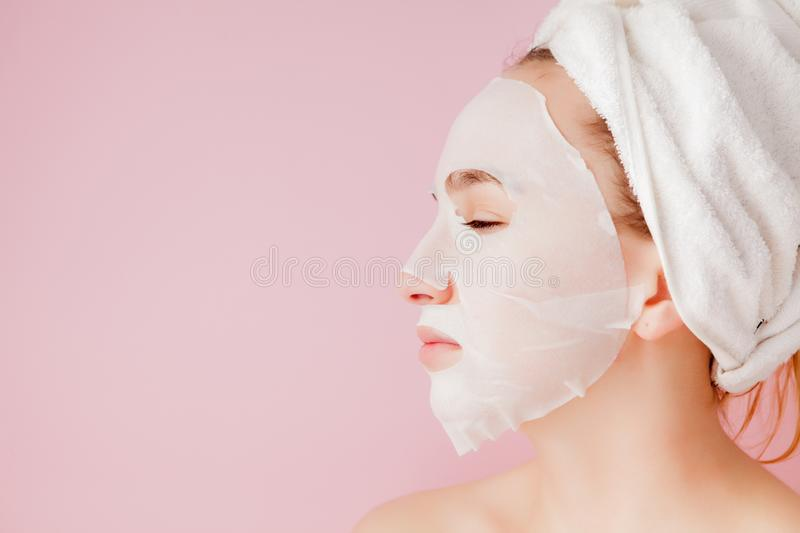 Beautiful young woman is applying a cosmetic tissue mask on a face on a pink background. Healthcare and beauty treatment and. Technology concept stock images