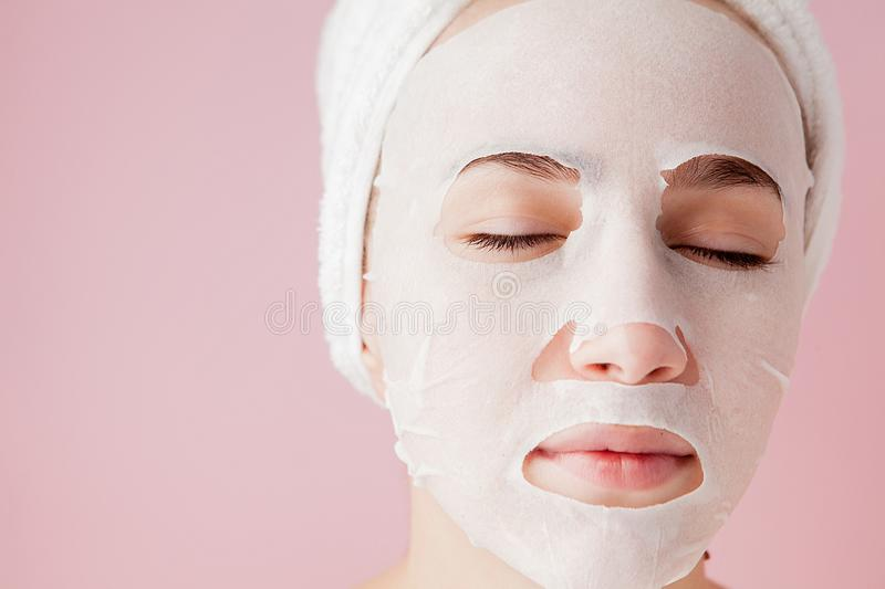 Beautiful young woman is applying a cosmetic tissue mask on a face on a pink background. Healthcare and beauty treatment and. Technology concept stock photos