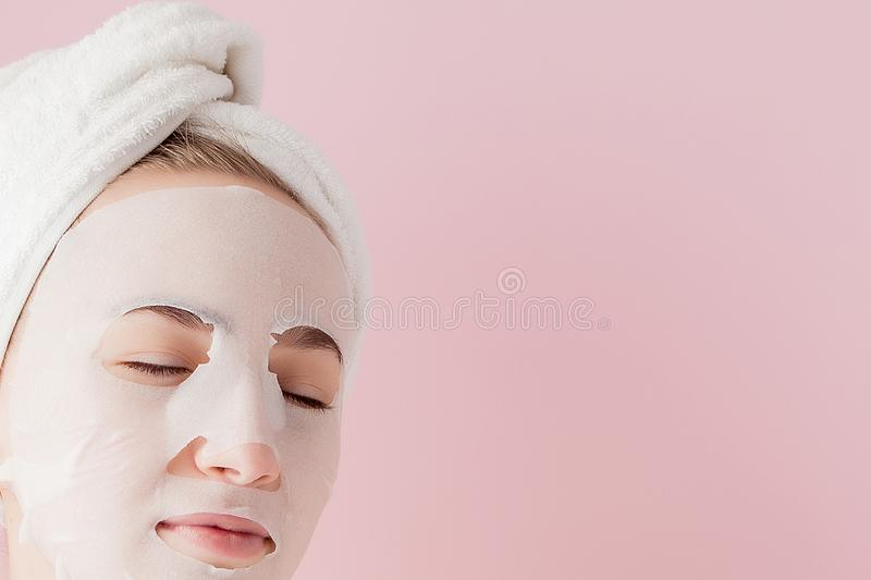 Beautiful young woman is applying a cosmetic tissue mask on a face on a pink background. Healthcare and beauty treatment and stock images