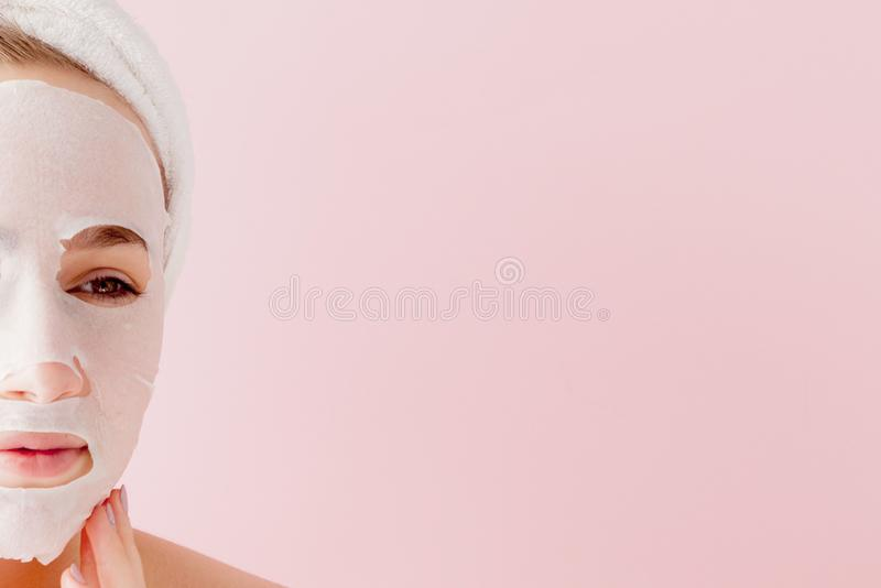 Beautiful young woman is applying a cosmetic tissue mask on a face on a pink background. Healthcare and beauty treatment and stock photo