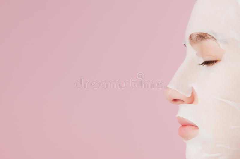 Beautiful young woman is applying a cosmetic tissue mask on a face on a pink background. Healthcare and beauty treatment stock photos
