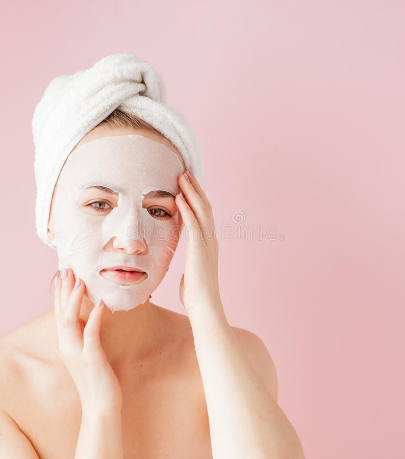 Beautiful young woman is applying a cosmetic tissue mask on a face on a pink background. Healthcare and beauty treatment and. Technology concept stock photography