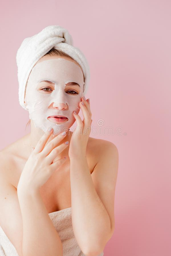 Beautiful young woman is applying a cosmetic tissue mask on a face on a pink background. Healthcare and beauty treatment and. Technology concept stock photo