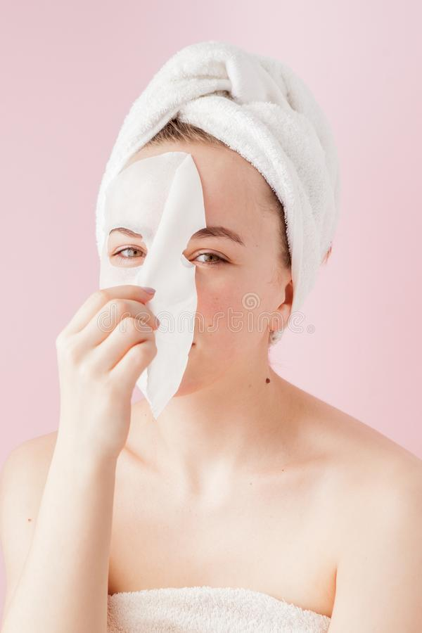 Beautiful young woman is applying a cosmetic tissue mask on a face on a pink background. Healthcare and beauty treatment and. Technology concept royalty free stock image