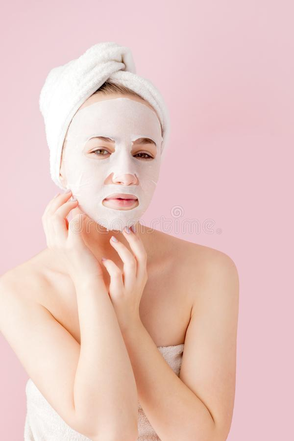 Beautiful young woman is applying a cosmetic tissue mask on a face on a pink background. Healthcare and beauty treatment and. Technology concept royalty free stock photos