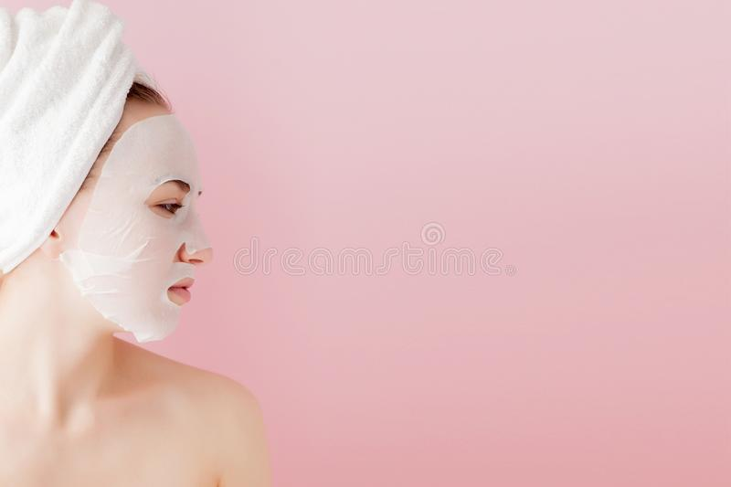 Beautiful young woman is applying a cosmetic tissue mask on a face on a pink background. Healthcare and beauty treatment and. Technology concept royalty free stock photography