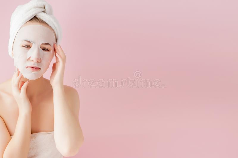 Beautiful young woman is applying a cosmetic tissue mask on a face on a pink background. Healthcare and beauty treatment and royalty free stock photo