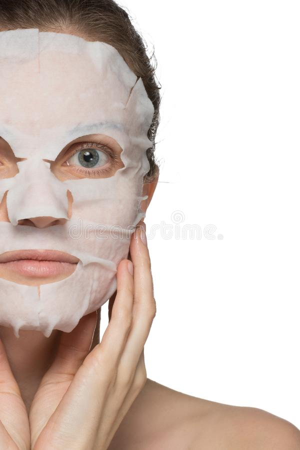 Beautiful young woman is applying a cosmetic mask on a face on a royalty free stock photo