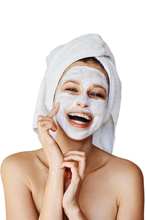 Beautiful young woman applying facial mask on her face. Skin care and treatment, spa, natural beauty and cosmetology concept, royalty free stock image