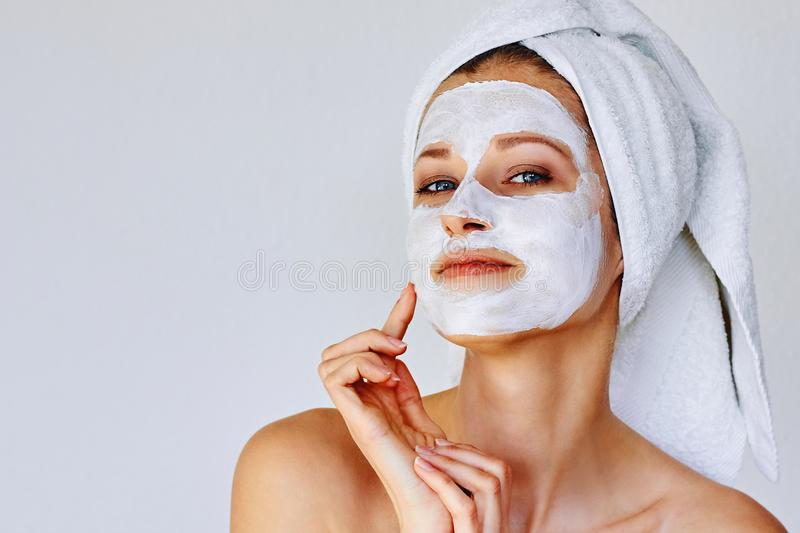 Beautiful woman applying facial mask on her face. Skin care and treatment, spa, natural beauty and cosmetology concept stock photography