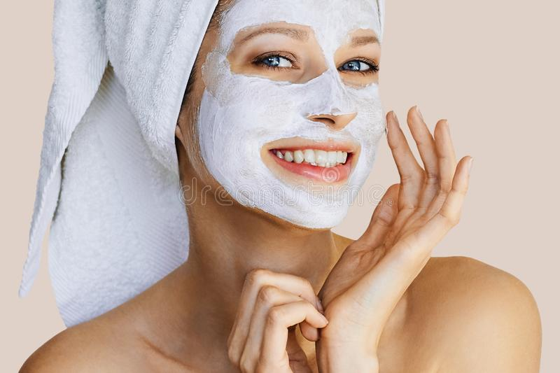 Beautiful young woman applying facial mask on her face. Skin care and treatment, spa, natural beauty and cosmetology concept stock images