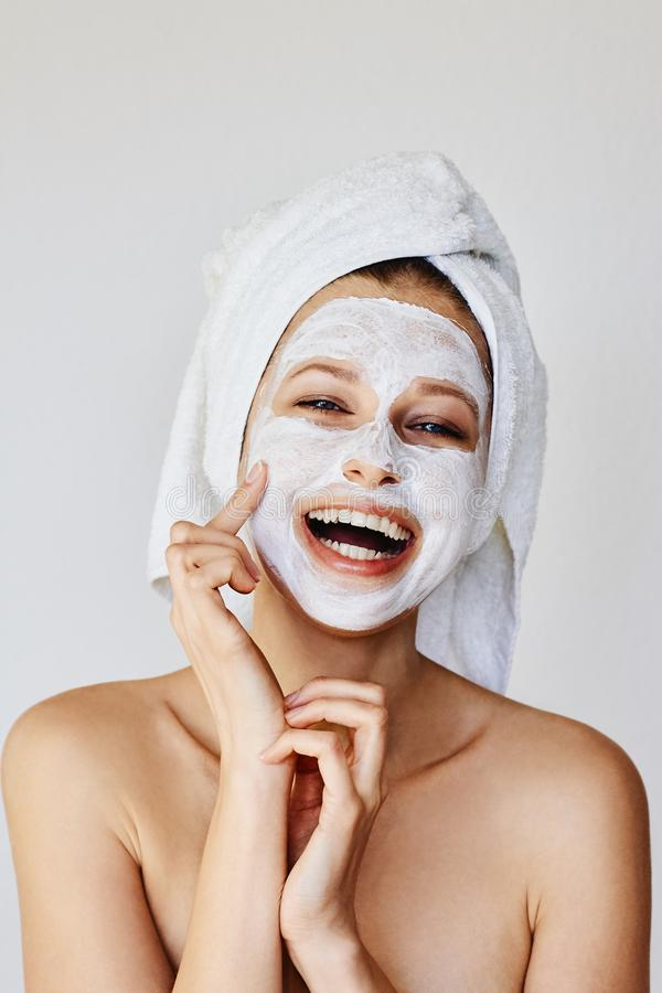 Beautiful young woman applying facial mask on her face. Skin care and treatment, spa, natural beauty and cosmetology concept royalty free stock photos