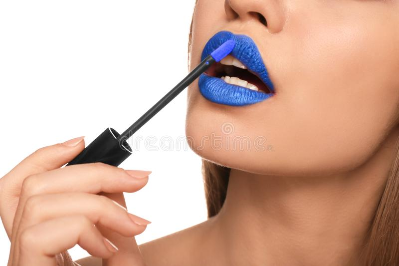 Beautiful young woman applying unusual lipstick on white background, closeup royalty free stock photos